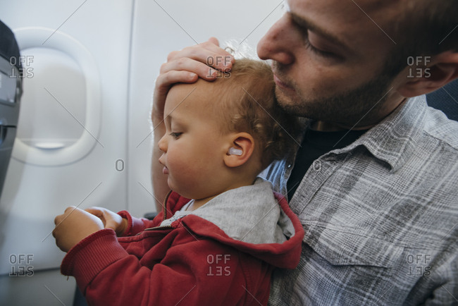 Father and son with earplugs during flight