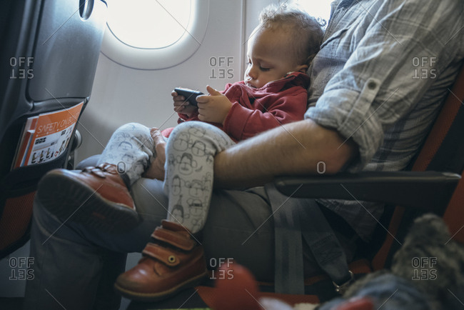 Young  with a phone seating on his father lap during flight