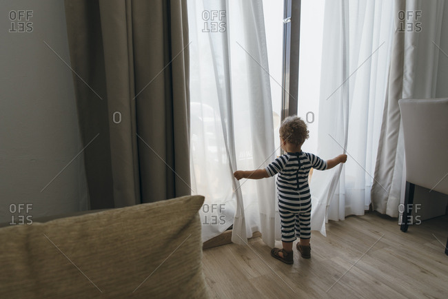 Young boy playing with sheer curtains in hotel room