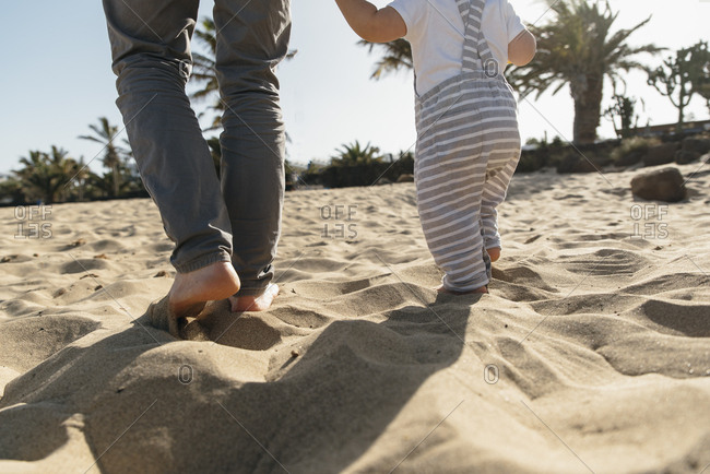 Close-up on bare feet of father and his son at the beach