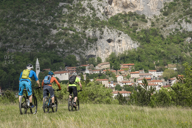 Mountain bikers riding cycle and overlooking houses by rocky mountain
