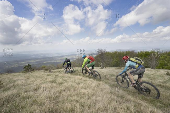 Biker riding bikes through grass on mountain