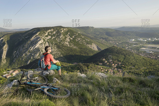Biker sitting on rock and looking at distance