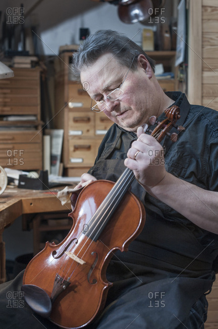 Violin maker polishing violin in workshop