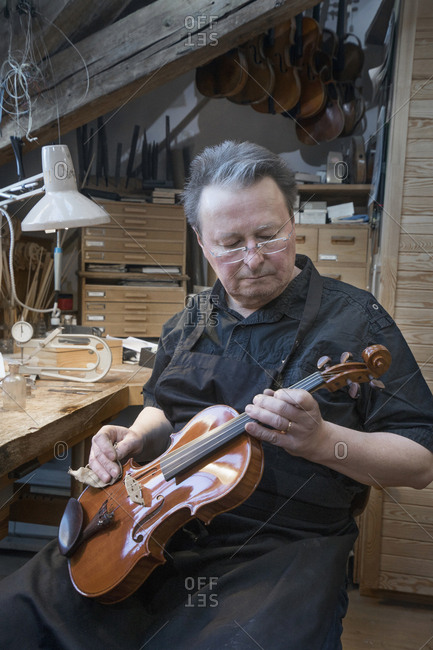 Violin maker polishing violin