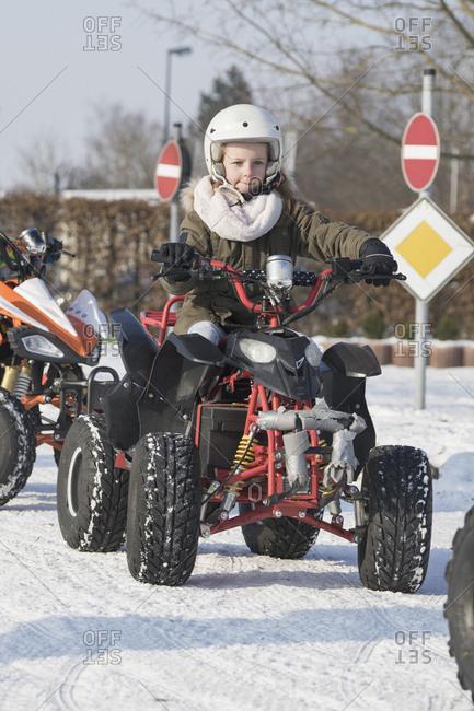 Girl riding quadbike on snow
