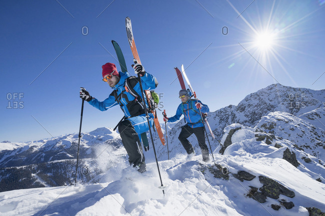 Skiers walking downwards on mountain slope