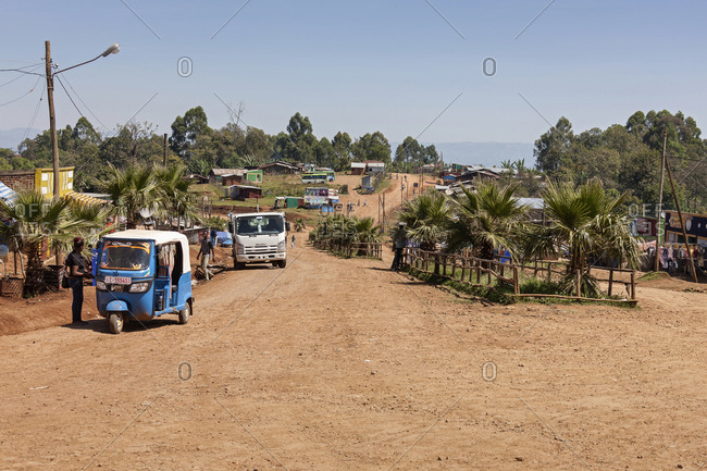 Bonga, Ethiopia, Africa - December 6, 2016: Jinrikisha on dirt road with other vehicles and trees against sky