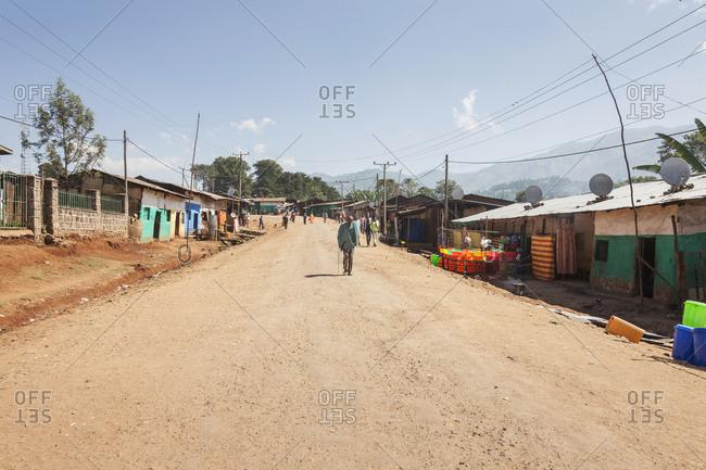 Hawassa, Ethiopia, Africa - December 10, 2016: People walking on dirt road by houses