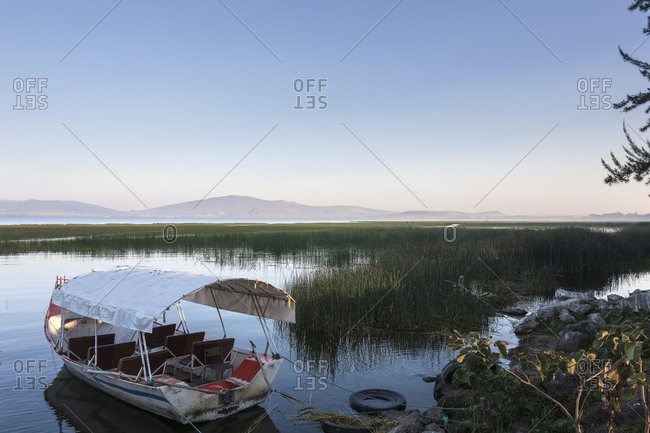 Boat anchored on lake by grass with mountains in background against clear sky