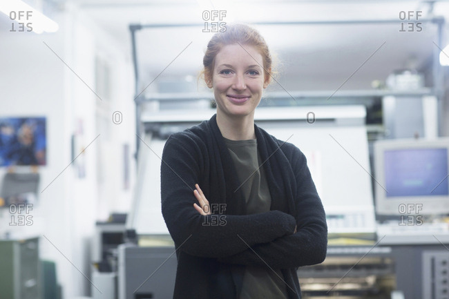 Portrait of woman with arms crossed standing by machinery at press
