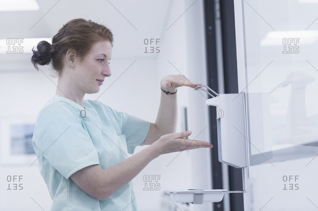Side view of hospital nurse disinfecting hands