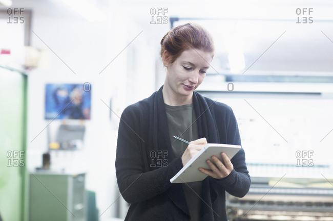 Female worker preparing list at printing press