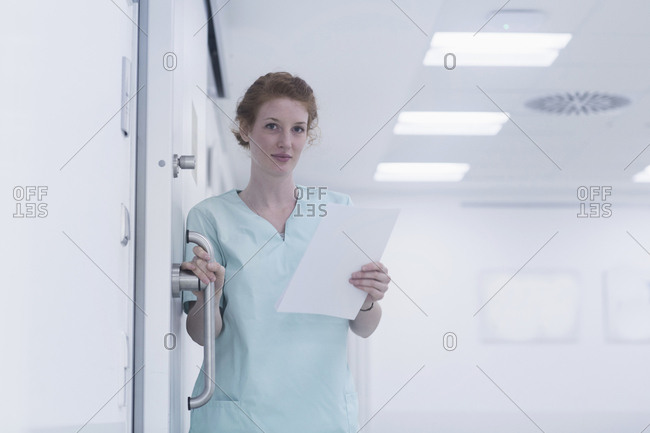 Portrait of nurse holding  handle of door and medical charts