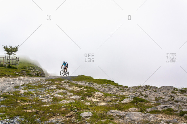 Mountain biker riding on dirt track by rocky slope