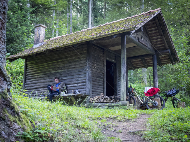 Mountain biker reading magazine while sitting in front of a cabin in the woods