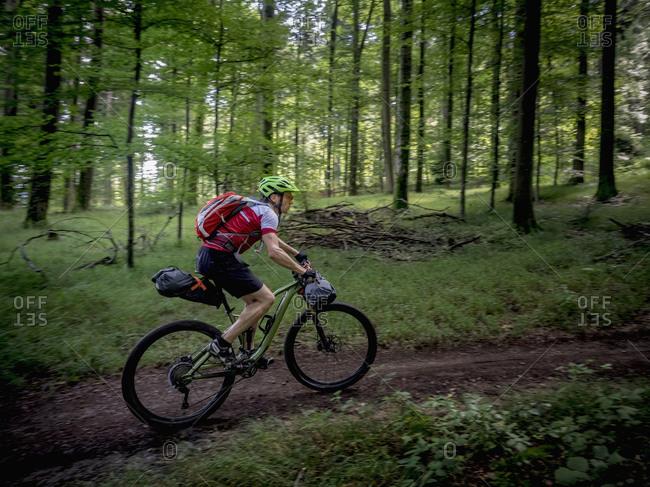 Mountain biker riding on a full suspension mountain bike through forest