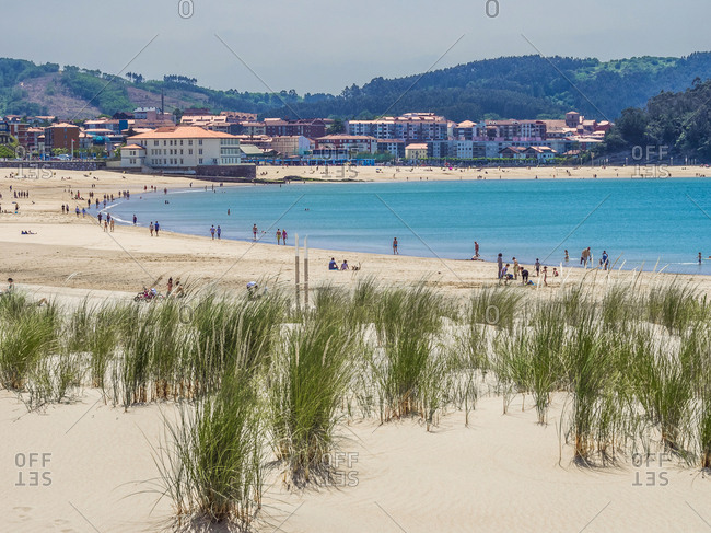 People at beach with houses and hills in background