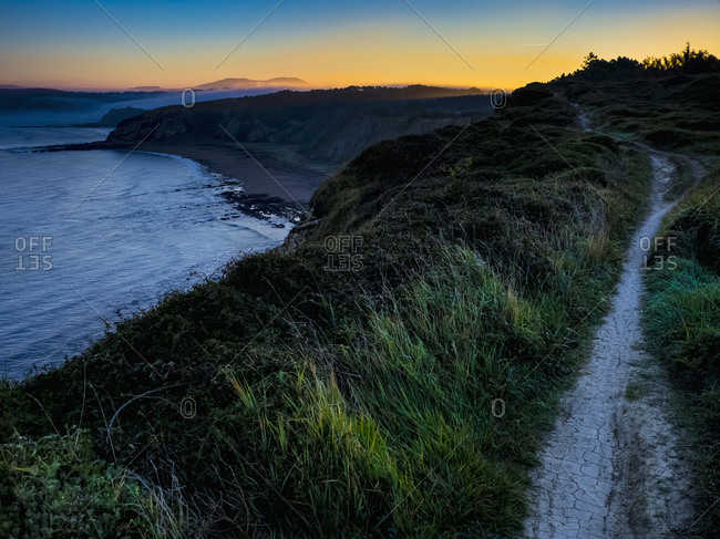 Single trail on cliff by sea at sunrise