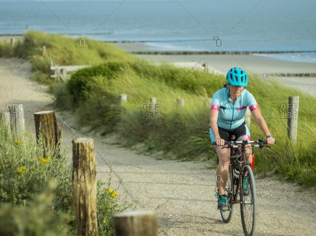 Woman riding bike near beach and sea