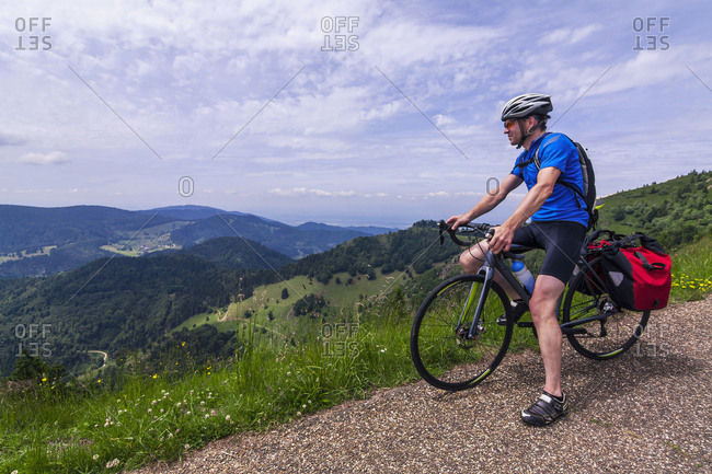 Man sitting on bicycle looking at mountains