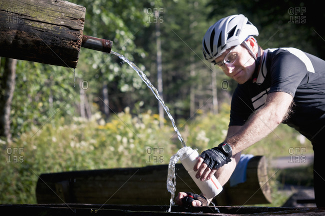 Biker filling water bottle in forest