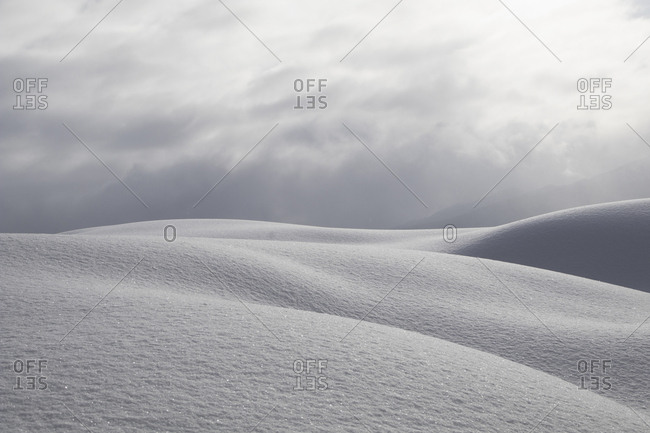 Powdered snow dune against cloudy sky