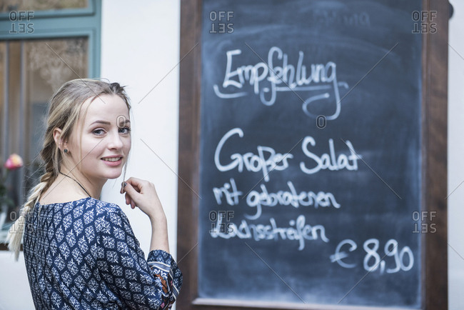 Portrait of young woman standing in front of chalkboard menu