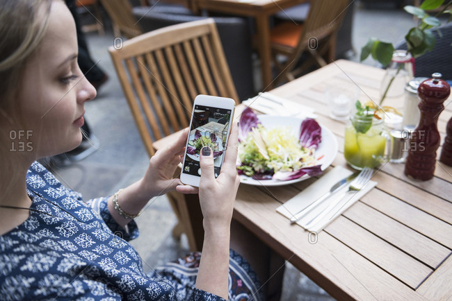 Young woman photographing salad