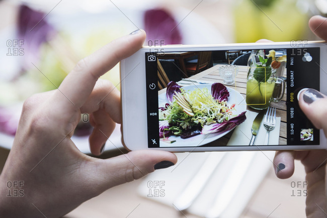 Hands of woman taking picture of mocktail and salad