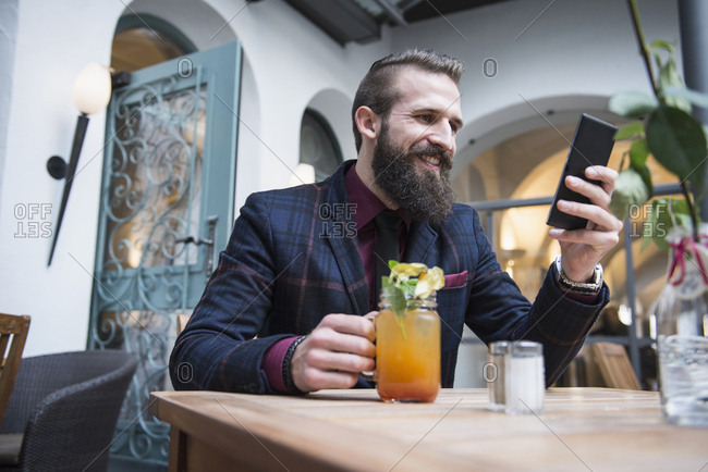 Young man using mobile phone while holding mocktail jar