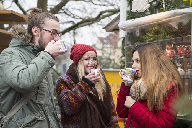 Friends drinking mulled wine at Christmas market