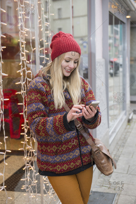 Young woman on glass and messaging on mobile phone