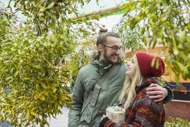 Couple embracing under mistletoe tree
