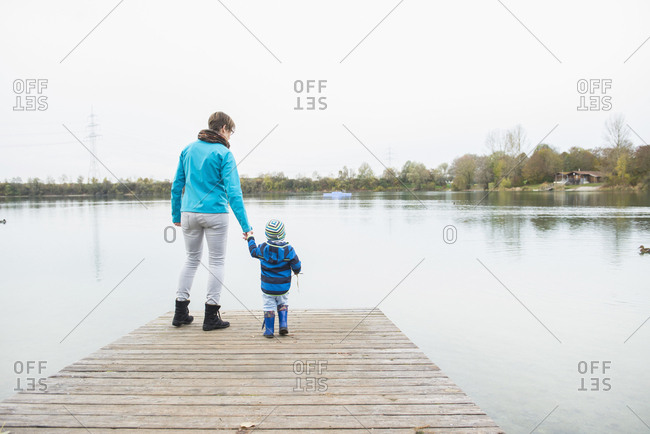Rear view of mother and son standing on wooden jetty overlooking lake and trees against sky