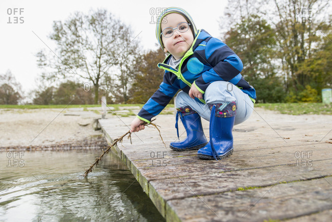 Boy crouching on jetty over lake while holding branch into water