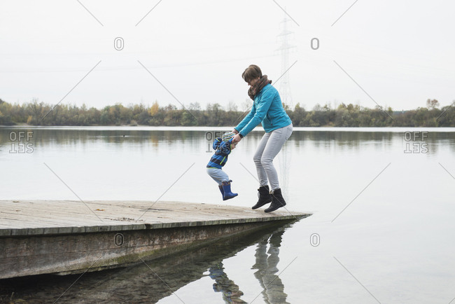Mother and son jumping hand in hand on a landing stage at a lake in the autumn