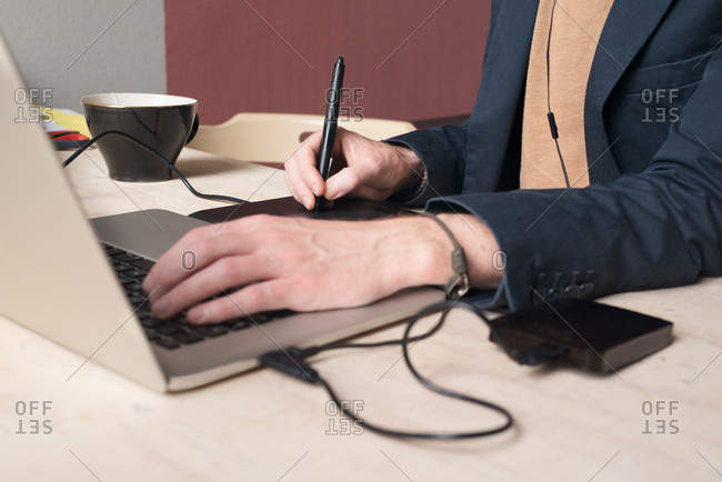 Close up of man using graphic drawing tablet on laptop