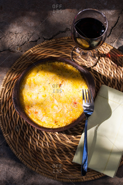 Overhead view of a frittatta dish with glass of red wine