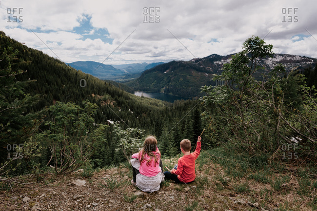 Two young children sitting on a hillside overlook