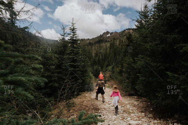 Children hiking with their father on a mountain trail