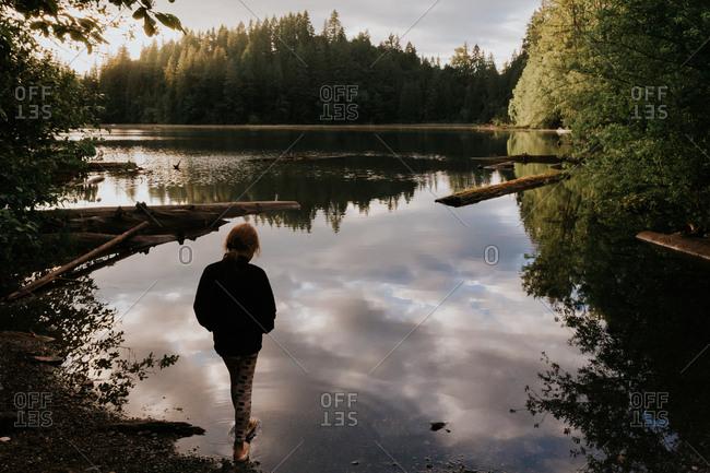 Girl wading in a lake at dusk