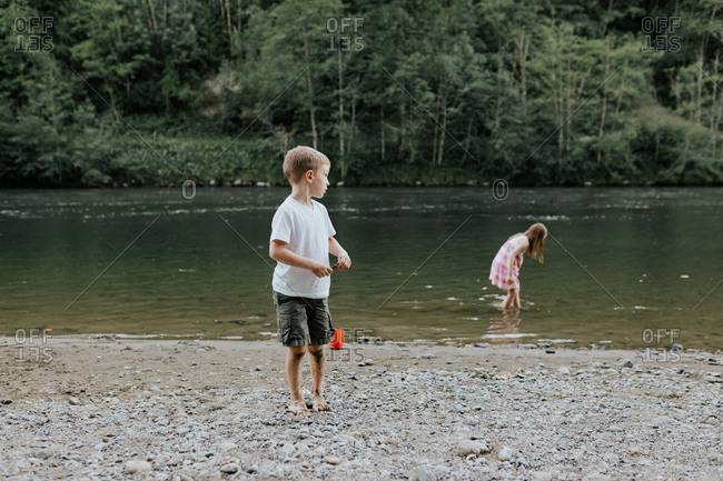 Two young children playing on a riverbank