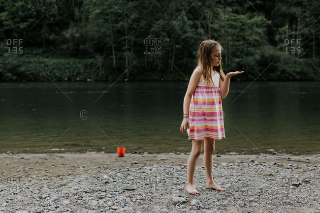 Girl looking at her discovery on the riverbank