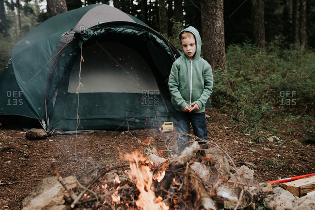 Young boy standing by fire at his campsite