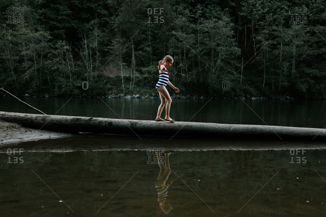 Young girl balancing on a fallen log in river