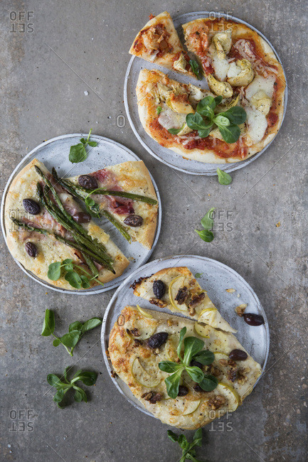 Trio of pizzas, Tomato base, mozzarella, artichoke and lamb lettuce garnish. White base pizza, Parma ham, asparagus, and olives, watercress garnish