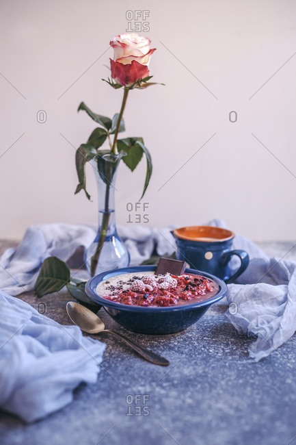 Porridge with raspberry sauce topped with frozen raspberries, cacao nibs and dark chocolate in a blue bowl
