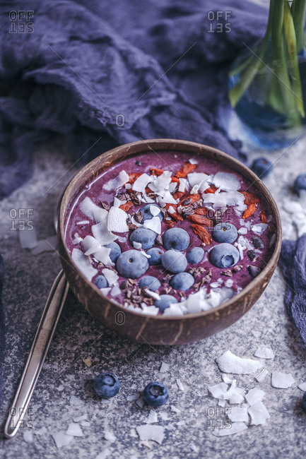 Blueberry smoothie topped with coconut flakes, goji berries, cacao nibs and blueberries in coconut bowl