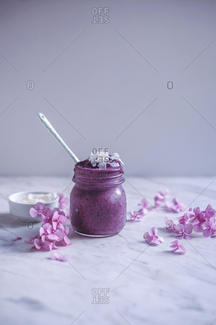 Blueberry banana ice cream topped with coconut flakes in a glass jar